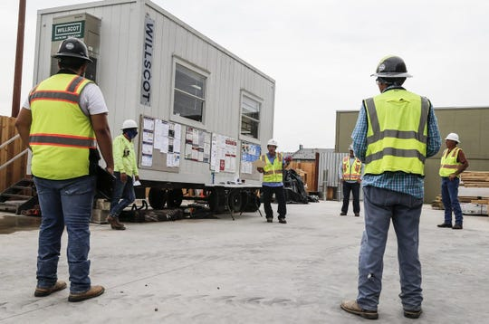 Job site superintendent Nathan Stanford talks with workers Thursday about coronavirus-related safety procedures at a construction site on Briarcliff Boulevard in East Austin.