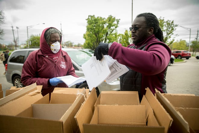 Armand Tatum, Western Hills High School football coach and teacher, helps hand out learning packets with Lezlie Christian, a theater and dance teacher, on Monday, April 13, 2020, outside the West Price Hill school.