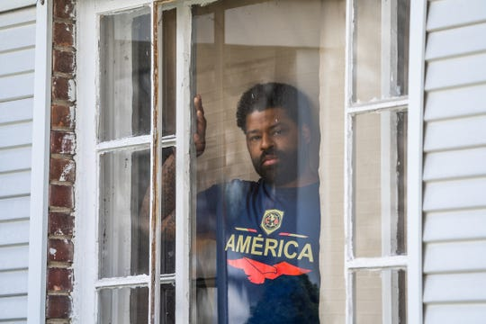 Keith Gambrell of Detroit is seen in a window in the front of his house while on quarantine with COVID-19 symptoms on Friday, April 10, 2020. Gambrell's life was ravaged after losing his grandfather and stepfather to COVID-19. His mother was hospitalized, and his younger brother is symptomatic, too.