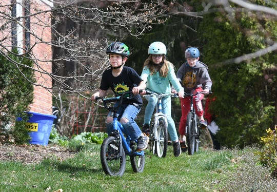 Nick Sloan, left, with his sister Sadie and brother Jack peddle along their own bike trail starting in their backyard and circling their Bloomfield Hills home on Friday.