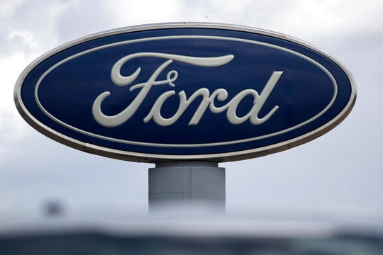 In this Sunday, April 5, 2020, photograph, the blue oval sign stands over a Ford dealership in Denver.