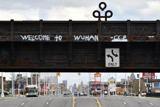 """Welcome to Wuhan"" is seen spray painted on a train bridge over Woodward Avenue in Highland Park on April 13, 2020."