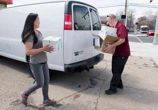 Lincoln Garden Chinese Restaurant owner Jenny Zhang, left, and Ascension St. Vincent employee Robert Kincaid, right, carry N95 masks donated by Zhang to help with the shortage of supplies Monday afternoon, March 23, 2020.