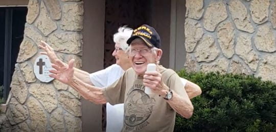 Robert Weaver smiles with delight as a parade of Lee County Sheriff's Office units and members of Grace Church pass by his home Saturday in honor of his 90th birthday.