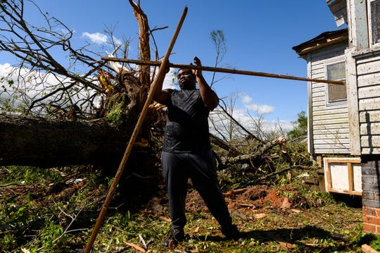 Jermaine Gaines cleans up debris from his yard after a tornado destroyed much of his childhood home in Seneca Monday, April 13, 2020.