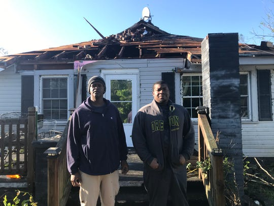 Jermaine Gaines, right, and Frederick Oglesby stand outside Gaines' childhood home on 4th St. in Seneca on Monday, April 13, 2020.