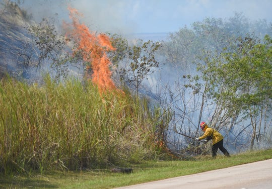 A firefighter from the Guam Department of Agriculture Guam Forestry and Soil Resources Division works to extinguish a fire near LeoPalace Resort Guam in Yona in this April 13 file photo.