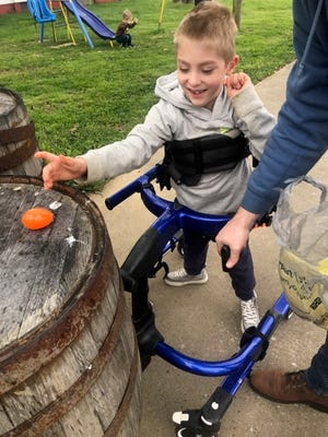 Blake Hargis checks out one of the sanitized eggs delivered to his house by the Brain Injury Adventure Camp, which had to get creative this year after their Egg Hunt was canceled due to the coronavirus.
