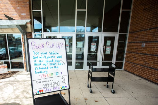 A whiteboard describing the book pick up process is seen, Monday, April 13, 2020, at the Public Library in Coralville, Iowa.