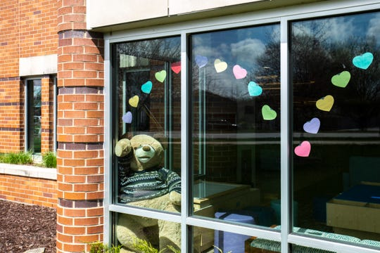 A large teddy bear is seen in a window decorated with cutout heart shapes, Monday, April 13, 2020, at the Public Library in Coralville, Iowa.