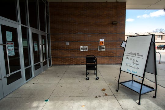 An empty library cart is seen outside the front door during a pickup time, Monday, April 13, 2020, at the Public Library in Coralville, Iowa.