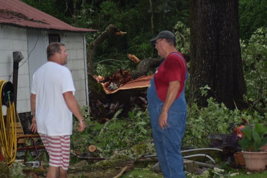 Steve Drummond talks with a neighbor who came to help after a tornado caused a tree to fall near Drummond's home a few miles south of Soso in northern Jones County, Sunday, April 12, 2020.