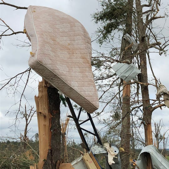 A mattress is impaled atop a snapped pine tree in Lawrence County after a powerful tornado killed a deputy sheriff and his wife and demolished their property during one of several Easter storms in Mississippi.
