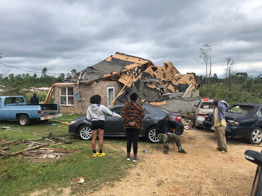 Lucky to be alive after the Easter tornado in Jefferson Davis County, residents stand outside a home on Granby Road where Jalissa Mikell, Noland Buckley and six others weathered the storm.