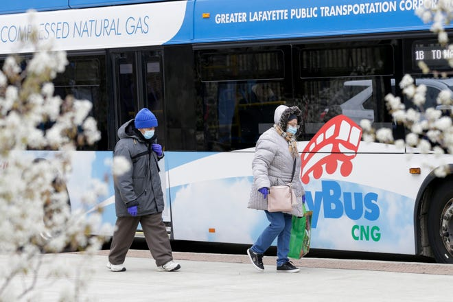A pair of riders walk towards a bus at the CityBus Center on Third Street, Monday, April 13, 2020 in Lafayette.