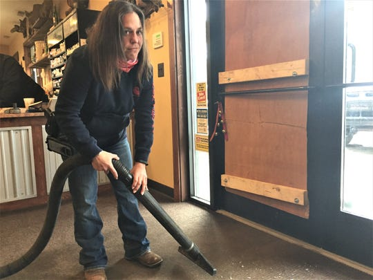 Unadilla Store employee Becky Saylor grimaces as she vacuums up broken glass next to a boarded up entry door, which was smashed. The store was broken in the early morning hours of April 13, 2020.
