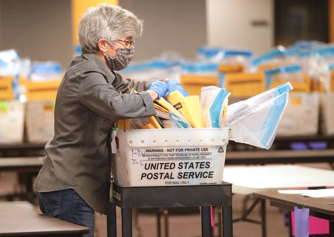Volunteer Anne DeLeo organizes ballots and documentation that goes with them for the April 7, 2020 election.