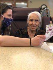 Becky Patterson, left, is helping a resident, Lila Swoverland, right, read a card at The Auberge at Oak Village in Menomonee Falls. Since residents can't have visitors, community members have sent them handmade cards.