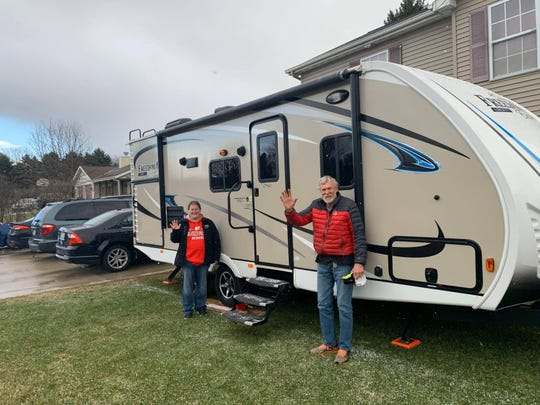 Tonia Hetzel and Jim Fiste stand in front of his travel trailer that is now set up in Hetzel's front yard in Sheboygan Falls. Hetzel, who works as en ER tech, is borrowing the trailer during the coronavirus pandemic so she can self-quarantine away from her family, which includes a son who has a compromised immune system.