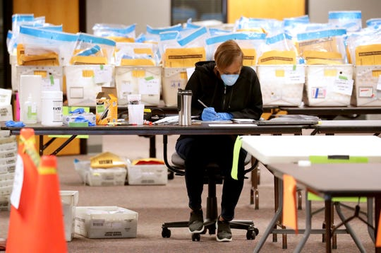 Stephanie Rushing, an election service coordinator with the Milwaukee Election Commission, counts ballots as workers were processing absentee ballots on the fourth floor of an office building at 501 W. Michigan Ave. on Monday.