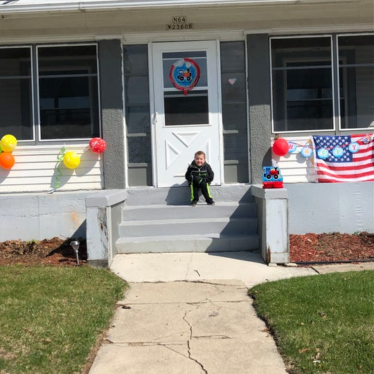 Dominic James Kilday, 5, is waiting outside his downtown Sussex home for the surprise parade to celebrate his birthday.  The Sussex, Lisbon and Merton fire departments drove through the village with more than 40 cars from community members.