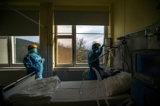 Medical staff members in protective suits check a ventilator at the care unit for COVID-19 infected patients inside the Koranyi National Institute of Pulmonology in Budapest on March 24. As health officials around the world push to get more ventilators to treat coronavirus patients, some doctors are moving away from using the breathing machines when they can.