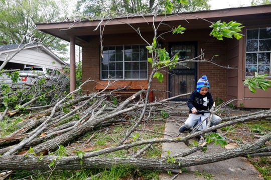 Athan Gonzalez, 6, plays outside his home where a tree fell Monday, April 13, 2020, in Cleveland, Miss. Overnight severe weather destroyed homes and businesses.