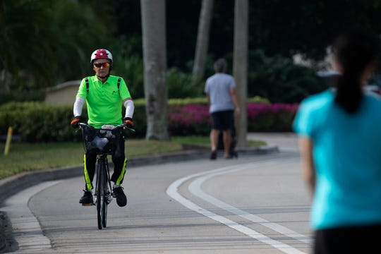 A bike rider shares the bike lane with  pedestrians as they exercise along Gulf Shore Boulevard North on Friday, April 10, 2020, in Naples.