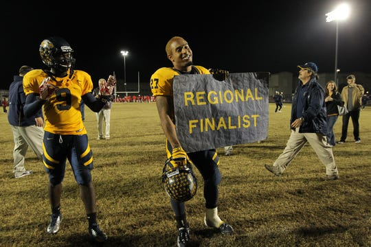 Naples High School running back Manny Morgan (27) holds a sign bearing his team's accomplishment after defeating South Fort Myers in the 2012 Class 6A Region 3 semifinal.