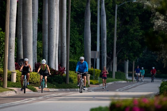 Molly Maxson, left, Julie Verry and Dean Davidson ride down Gulf Shore Boulevard North in Naples on Friday, April 10, 2020.