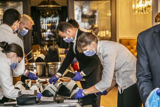 Enployees at Sails Restaurant in Naples don face masks as they prepare food for a charitable donation to health care workers.