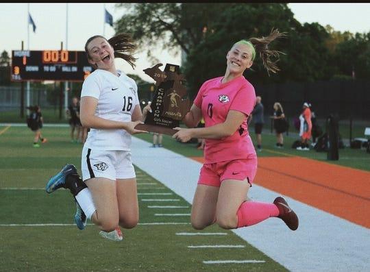 Emma Lennig, left, celebrates Plymouth girls soccer's division title.