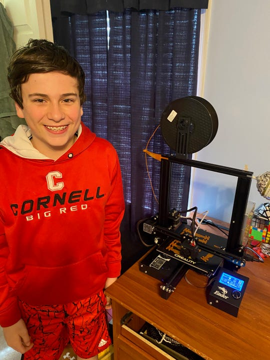 Ryan Cleck, 12, with his 3D printer.