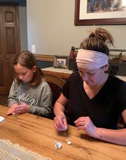 Emma McIntyre, 9, and her mom Nicole McIntyre make gnomes together at their home in Melvin to sell for donations for the Yale Community Food Fund.