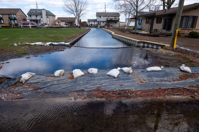 Sandbags form part of a barrier to keep water from coming over an Algonac road Friday, April 10, 2020.