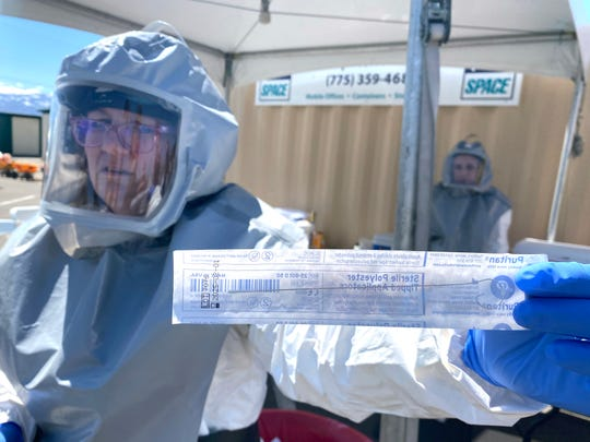 A nurse from the Washoe County Health District holds a swab during a mock COVID-19 swabbing at the Reno-Sparks Livestock Events Center on Monday, April 13.