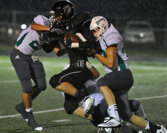 Grape Creek High School's Jacob Schmidt is tackled by Bangs defenders during a 2012 game.