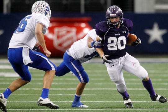Mason High School's Rio Schmidt tries to avoid a tackle by a Stamford player during the Class 1A Division I State Championship at Cowboys Stadium on Dec. 15, 2011.