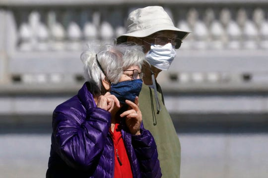 Reva and Mac Anderson walk around the Utah State Capitol Friday, April 10, 2020, in Salt Lake City. The state's total number of positive cases reached 28,855 on Saturiday, with 1,797 hospitalizations and 212 confirmed deaths. (AP Photo/Rick Bowmer)