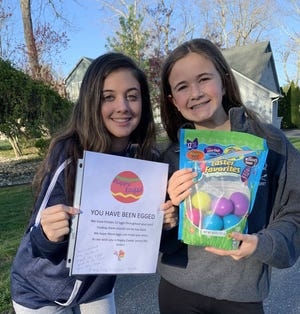 "Corinne Vicente, (left) a junior at Our Lady of Mercy Academy, and her sister, Carly, ""EGG"" the homes of relatives by leaving special Easter goodies outside their homes."