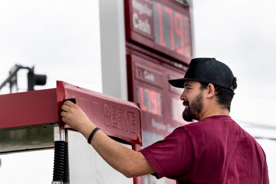 Freddy Espinoza changes signage on a fuel pump at Jack's Liquor in Farmersville on Monday, April 13, 2020. It is one of three stations on the corner with unleaded at $1.799 a gallon. Prince Gas had it for $1.759 the same day.