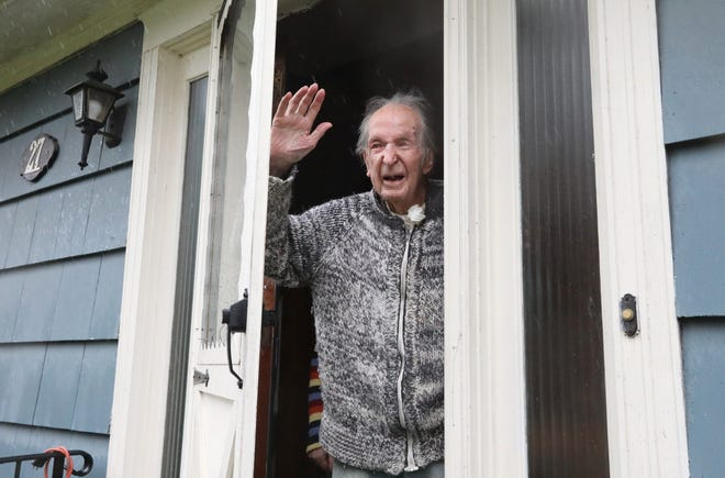 Alan Cameron waves to people driving by his Pearl River, New York, home to congratulate him on his 101st birthday April 13, 2020.