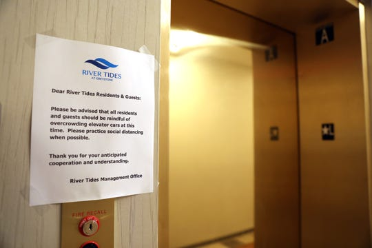 A sign reminds residents to keep a social distance beside the elevator door at River Tides apartment building in Yonkers April 13, 2020.