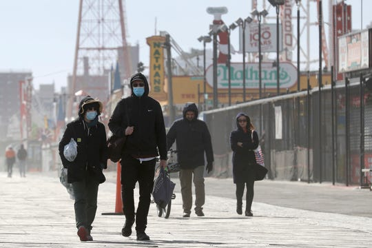 Pedestrians enjoy the warm weather on the boardwalk at Coney Island in New York, Sunday, April 12, 2020. Amid some signs of hope that the coronavirus infection rate is plateauing, New York is still wrapping up its worst week in deaths so far since the outbreak began.
