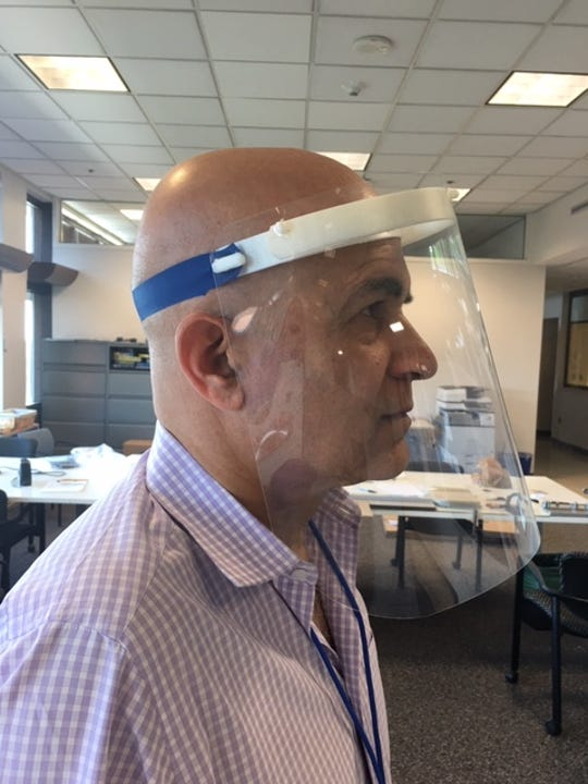 Tariq Rahman, principal research engineer at Nemours, models one of the reusable face shields using headbands built by 3D printers at the DuPont Experimental Station.