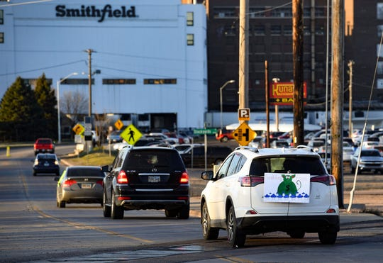 In this Thursday, April 9, 2020 photo, a sign depicting Smithfield Food, Inc. as a pig-shaped money bag is visible on the back of a car during a protest on behalf of employees calling for a safe and healthy workplace drives past Smithfield Foods, Inc. in Sioux Falls. during a protest on behalf of employees after many workers complained of unsafe working conditions due to the COVID-19 outbreak. The pork processing plant in South Dakota is closing temporarily after more than 80 employees tested positive for the coronavirus.