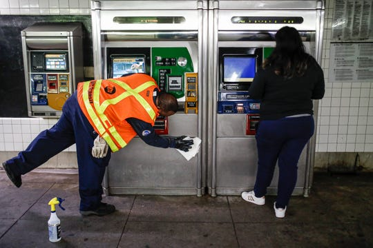 "An MTA employee sanitizes surfaces at the Classon Ave. and Lafayette Ave. subway station with bleach solutions due to COVID-19 concerns, Friday, March 20, 2020, in the Brooklyn Borough in New York. New York Gov. Andrew Cuomo is ordering all workers in non-essential businesses to stay home and banning gatherings statewide. ""Only essential businesses can have workers commuting to the job or on the job,"" Cuomo said."