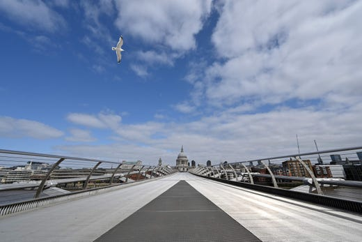A gull flies over a deserted Millennium Bridge near to St Paul's Cathedral in London on April 13, 2020, as life in Britain continues over the Easter weekend, during the nationwide lockdown to combat the novel coronavirus pandemic