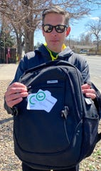 Denver hospital worker Kevin Long displays his backpack with stickers showing that he's had his temperature taken, to ensure he's not a risk to his colleagues or hospital patients during the coronavirus outbreak.