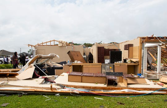 Neighbors inspect a house for occupants in Monroe, La., after an Easter tornado ripped through the town just before noon on April 12, 2020.